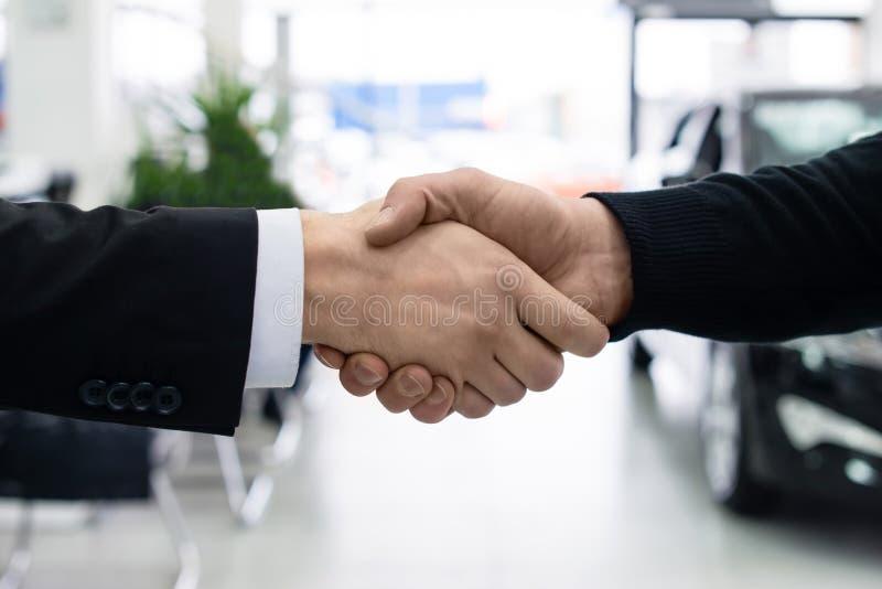 Männer rütteln Hände am Autohändlerausstellungsraum stockfotos