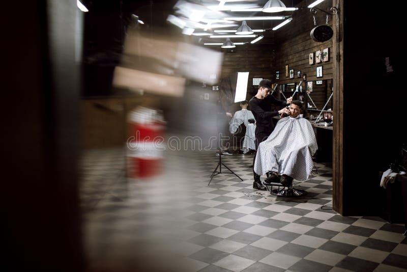 Männer ` s Art Der Modefriseur macht eine stilvolle Frisur für einen schwarz-haarigen Mann, der im Lehnsessel im stilvollen sitzt stockfoto