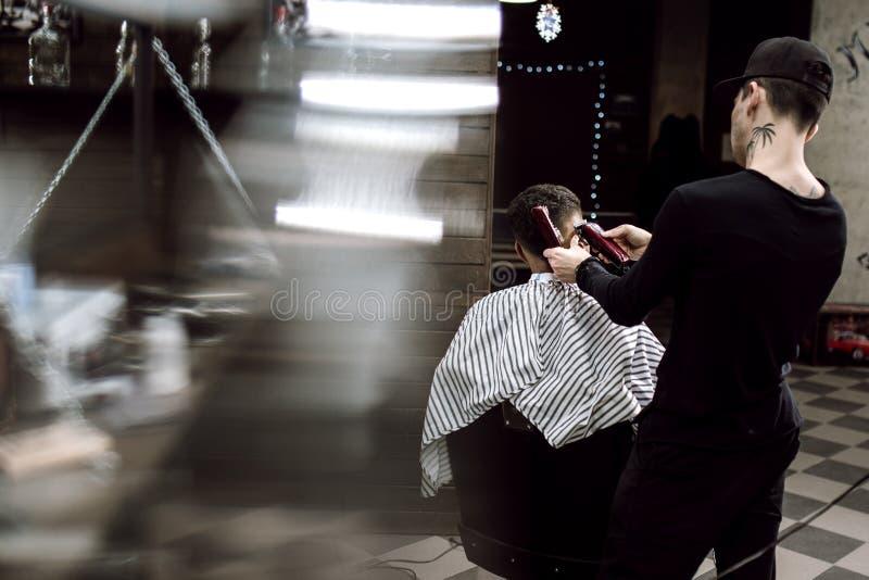 Männer ` s Art Der Modefriseur macht eine stilvolle Frisur für einen schwarz-haarigen Mann, der im Lehnsessel im stilvollen sitzt stockbild