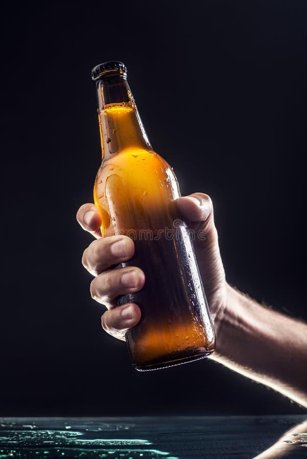 Männer ` s Hand, die eine Flasche Bier hält stockbilder