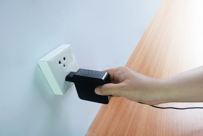 Männer ` s Hand hat Stecker, Adapter, Netzanschlusskabelstecker, Geräte auf Bretterboden lizenzfreies stockfoto