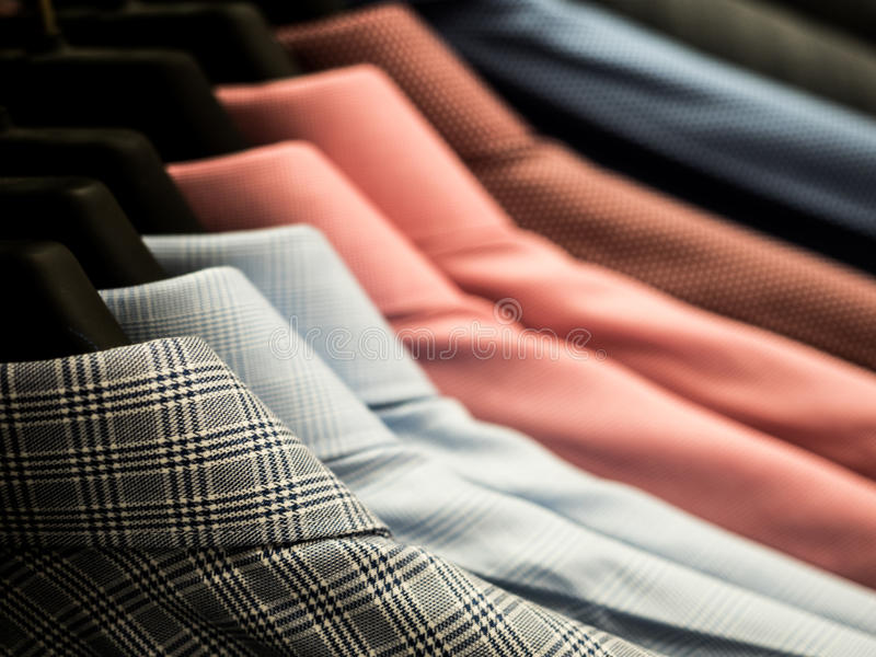Männer ` s Hemden, die am Gestell in einem Kaufhaus hängen lizenzfreies stockbild