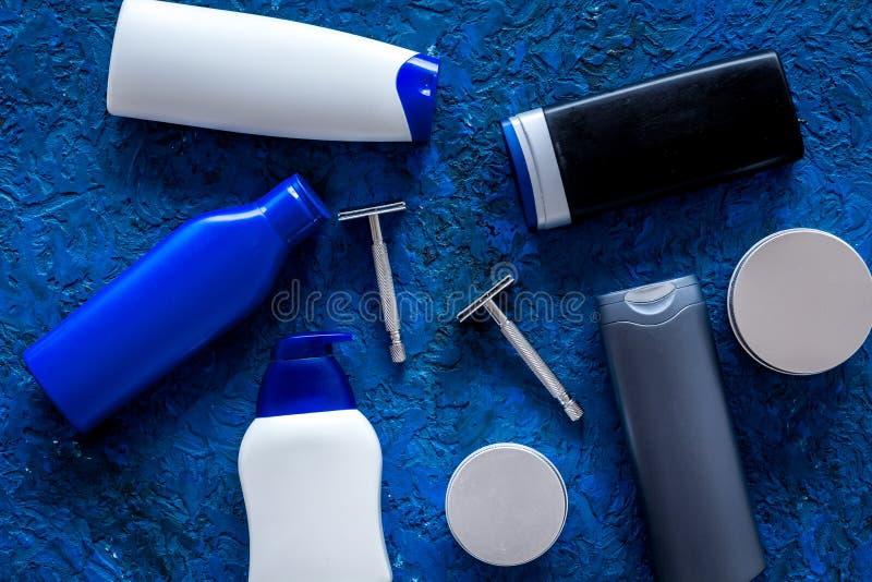 Männer ` s Kosmetik für Haarpflege und das Rasieren Shampoo, Gel, Rasiermesser, Wachs auf blauem copyspace Draufsicht des Hinterg stockfoto