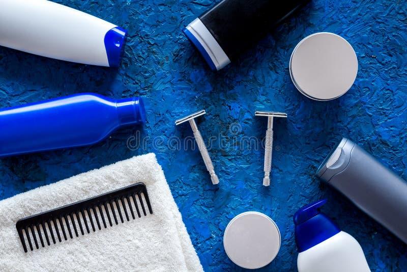 Männer ` s Kosmetik für Haarpflege und das Rasieren Shampoo, Gel, Rasiermesser, Wachs auf blauem copyspace Draufsicht des Hinterg stockfotos