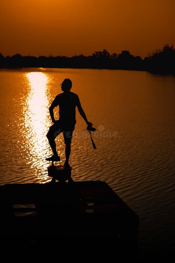 Männer sind am Rand des Reservoirs und des Ansicht-Reservoirs am Abend und am Sonnenuntergang stockbilder