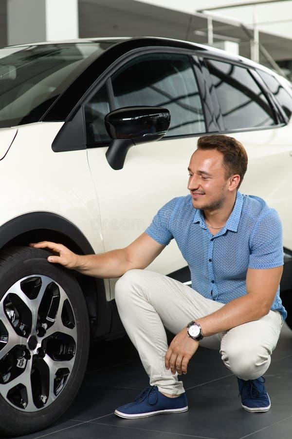 Männer sitzen nahe nagelneuem Auto lizenzfreie stockfotografie