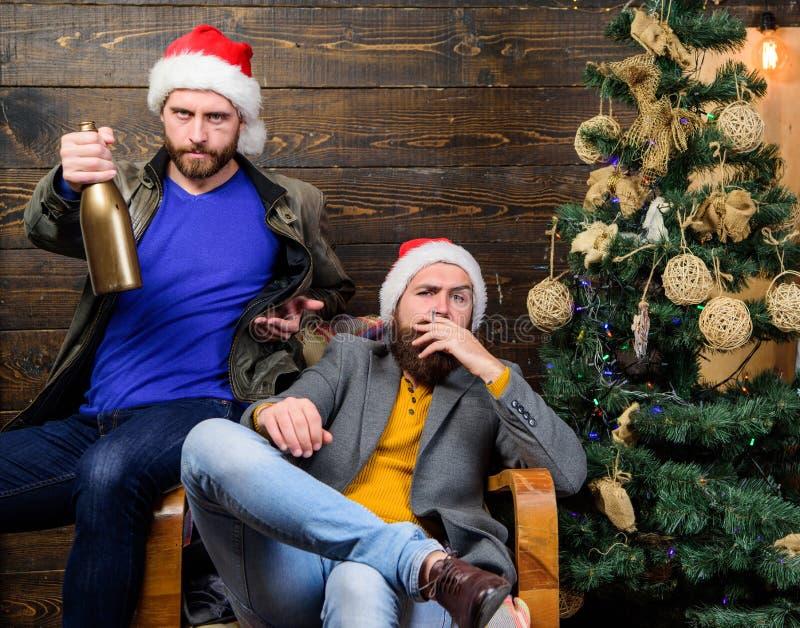 Männer trinken Champagner und das Rauchen Grobe Männer feiern neues Jahr nahe Weihnachtsbaum Neue Jahre Auflösung- E lizenzfreie stockbilder
