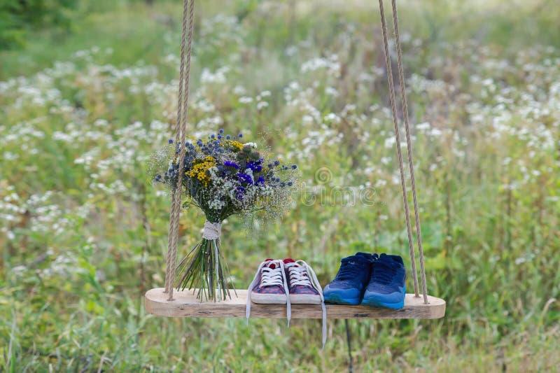 Männer und die Schuhe der Frauen mit einem hellen Blumenstrauß von Blumen draußen auf einem Schwingen, Geschenk, Valentinsgrußtag lizenzfreie stockbilder