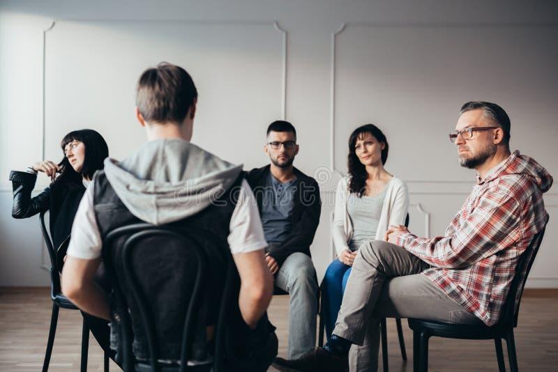 Männer und Frauen, die über Angstprobleme des Jugendlichen während der Gruppentherapie hören stockbilder