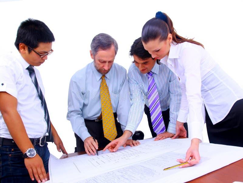 Männer und Frauen, die an Blaupausen arbeiten stockbilder