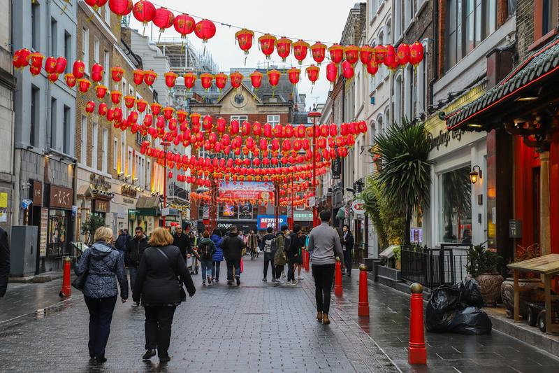 Männer und Frauen, die in Straßen in China-Stadt in London gehen stockfotografie