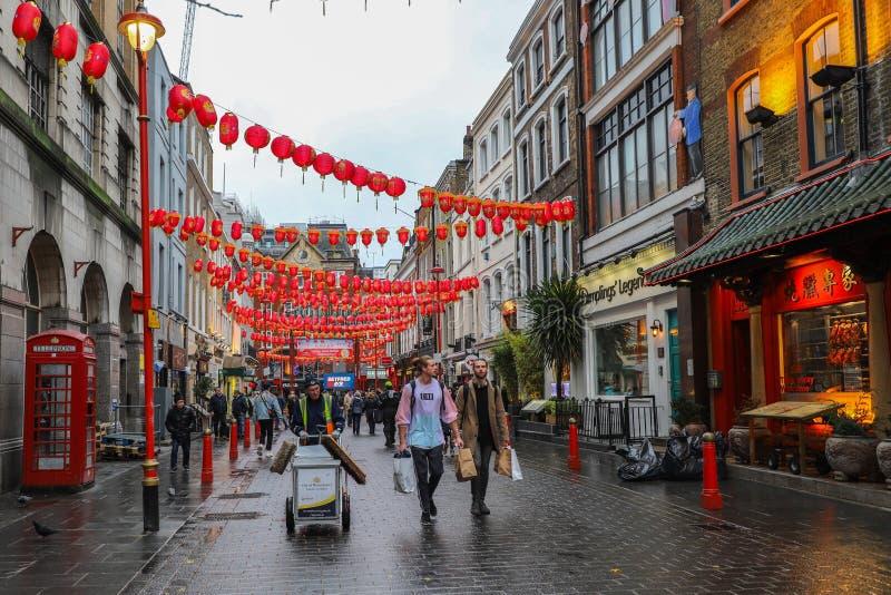 Männer und Frauen, die in Straßen in China-Stadt in London gehen lizenzfreie stockbilder