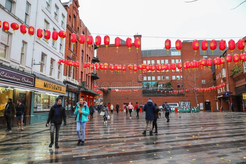 Männer und Frauen, die in Straßen in China-Stadt in London gehen stockbilder