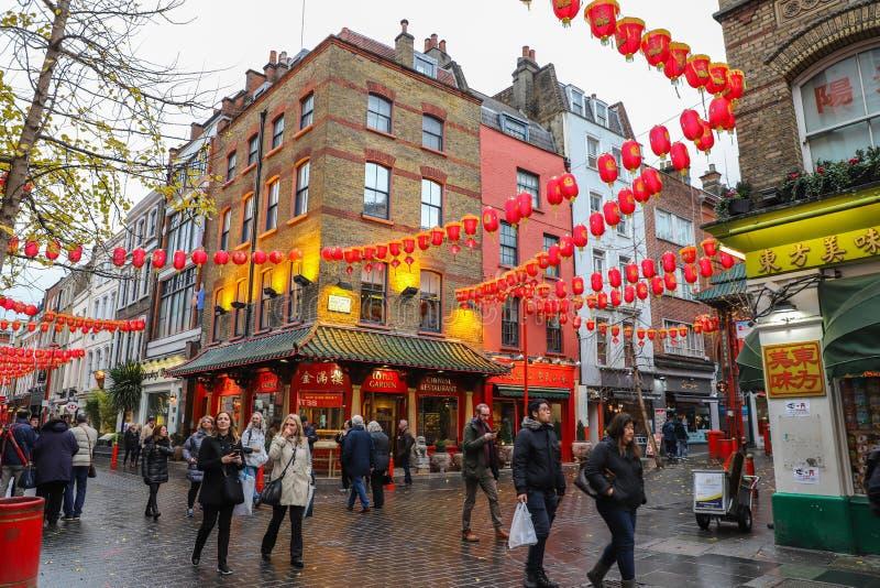 Männer und Frauen, die in Straßen in China-Stadt in London gehen stockbild