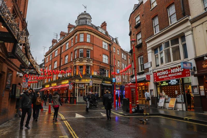 Männer und Frauen, die in Straßen in China-Stadt in London gehen lizenzfreie stockfotos