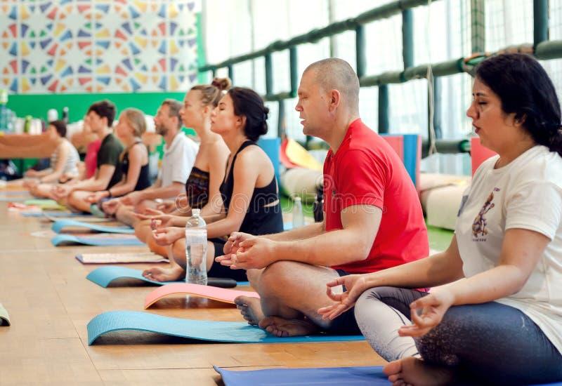 Männer und Frauen, welche die Praxis der Meditation, sitzend im asana innerhalb des Fitness-Clubs atmen und machen stockfoto