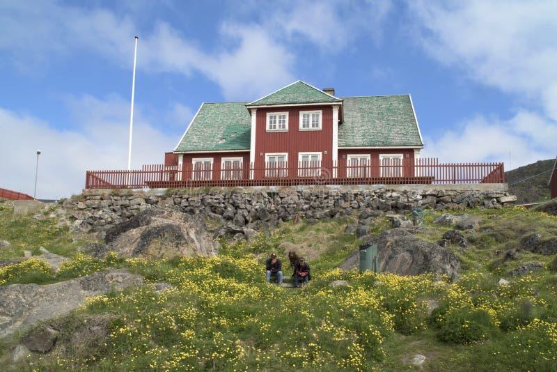 Männer vor rotem Haus, Grönland lizenzfreies stockbild