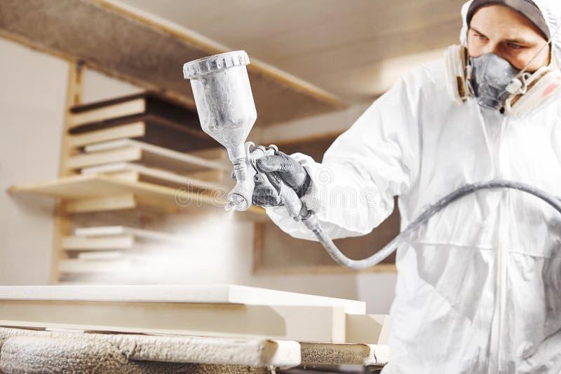 Människa som arbetar med sprutsprutlackspruta, flygfri sprutning till trä royaltyfria bilder