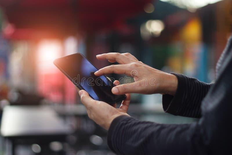 Människahänder genom att använda den mobila smartphonen i coffee shop arkivbilder