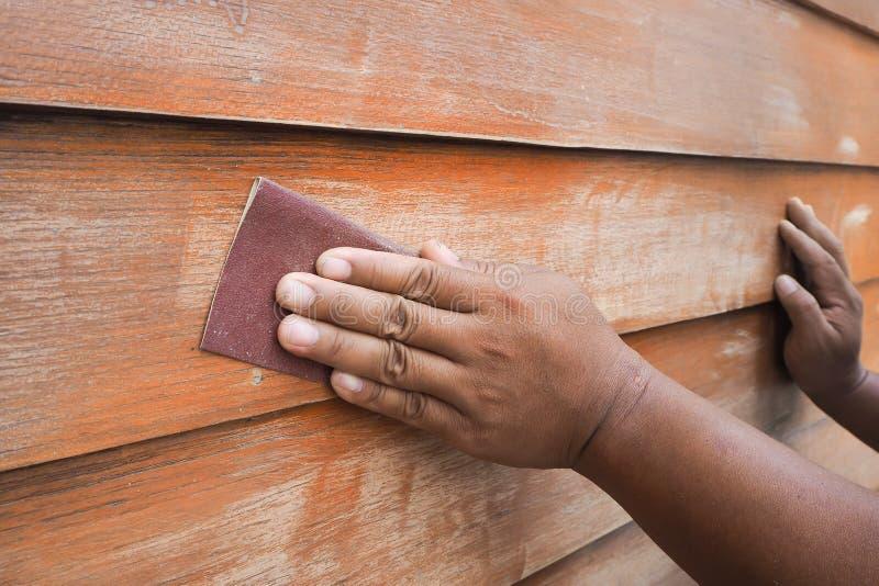 Människahänder som skurar den wood väggen vid sandpapper royaltyfri bild