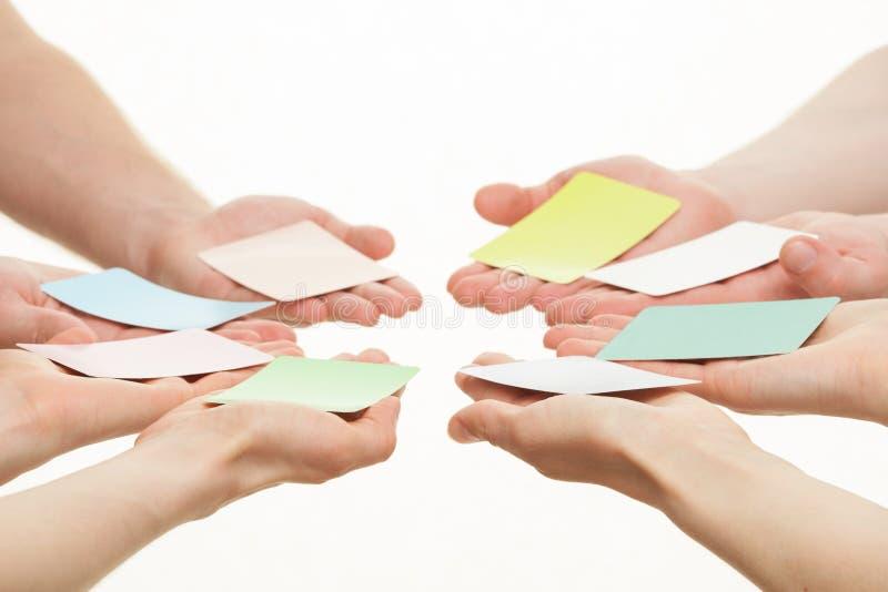 Människahänder som ut når färgrika pappers- kort royaltyfria bilder