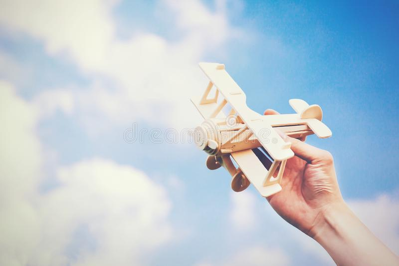Människan räcker att rymma en träplan leksak över blå himmel med copysp fotografering för bildbyråer