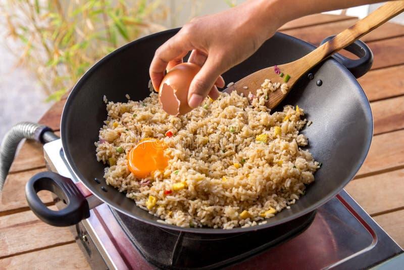 Människan räcker att tillfoga ägget in i stekte ris royaltyfria foton