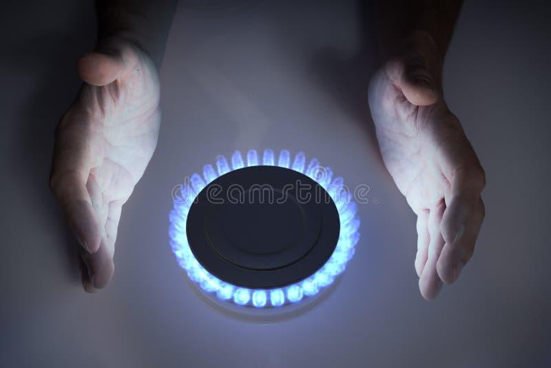 Människan värmer upp händerna nära blåpropankobutan gas på spisarna royaltyfri bild