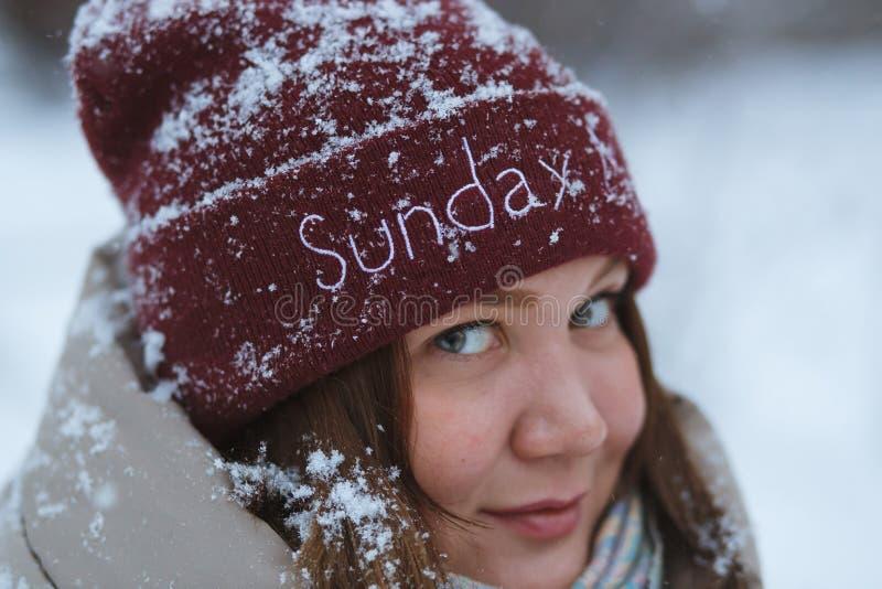 Människor, årstid och semestrar - skildring av lyckligt leende unga kvinnor utomhus i vinterparken Hon klädde sig i rött royaltyfri foto