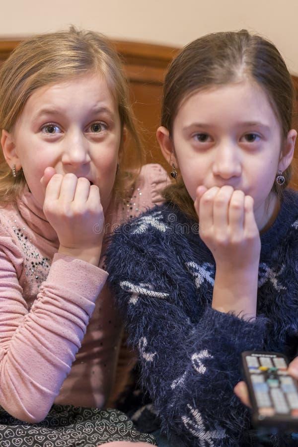 Människor, barn, TV, vänner och vänskap - två rädda små flickor som tittar på skräck i TV hemma Lodrät arkivfoton