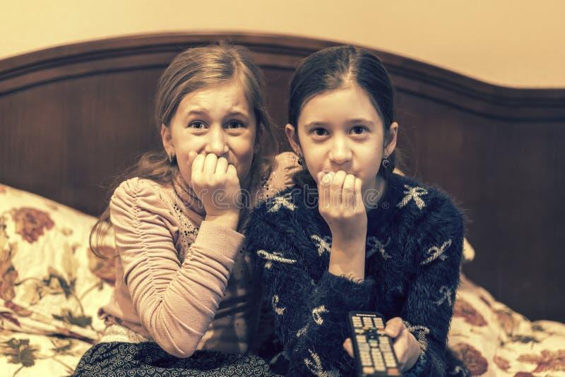 Människor, barn, TV, vänner och vänskap - två rädda små flickor som tittar på skräck i TV hemma tonad royaltyfri bild