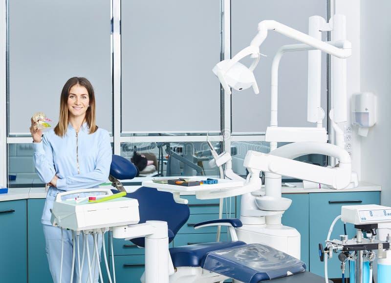 Människor, medicin, stomatologi och hälsovårdskoncept - en lycklig ung kvinnlig tandläkare med verktyg över läkarkåren arkivbild
