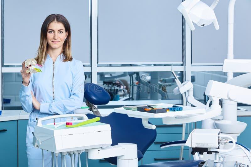 Människor, medicin, stomatologi och hälsovårdskoncept - en lycklig ung kvinnlig tandläkare med verktyg över läkarkåren arkivfoto