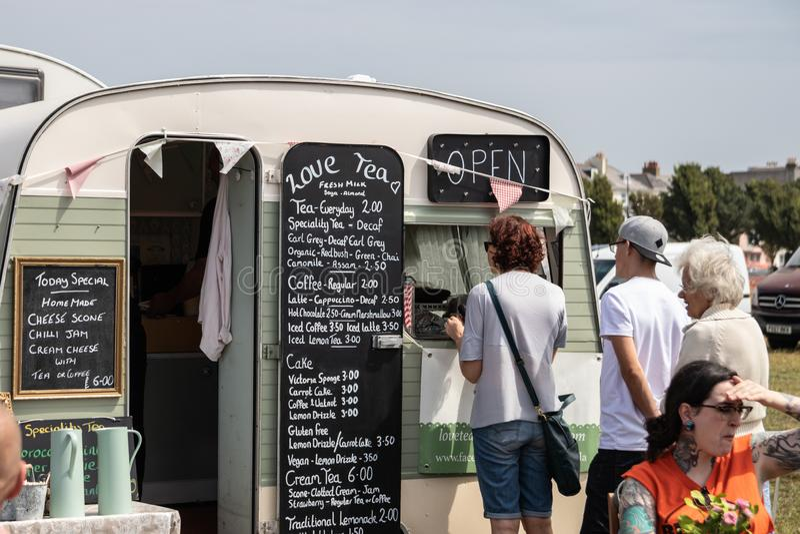 Människor som köar för te och kaffe i en vintage caravan omvandlad till ett mobilt kafé arkivbild