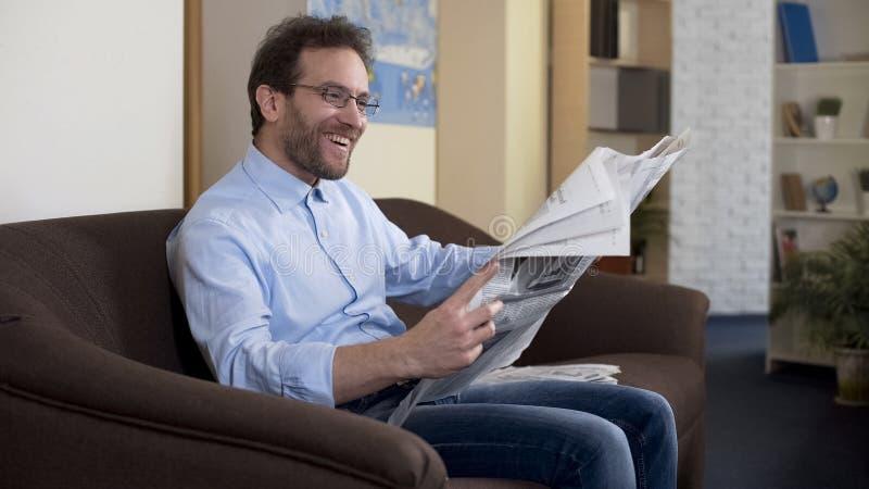 Männliche Ablesenzeitung der glücklichen Mittelvierziger, entspannte Person, die auf Sofa, Presse sitzt lizenzfreie stockfotos