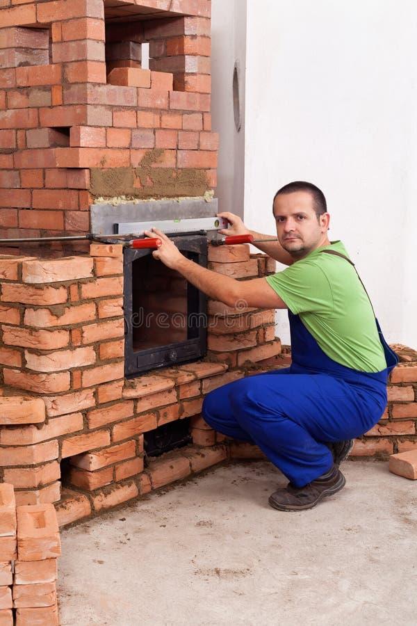 Männliche Arbeitskraft, die einen Kachelofen errichtet lizenzfreies stockfoto