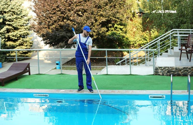Männliche Arbeitskraft, die Pool im Freien säubert lizenzfreie stockfotos