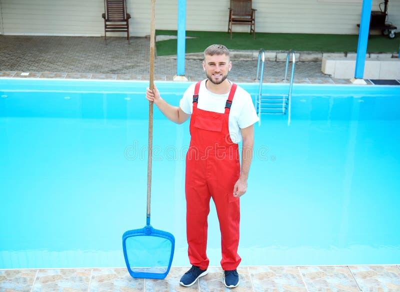 Männliche Arbeitskraft, die Pool im Freien säubert lizenzfreies stockbild