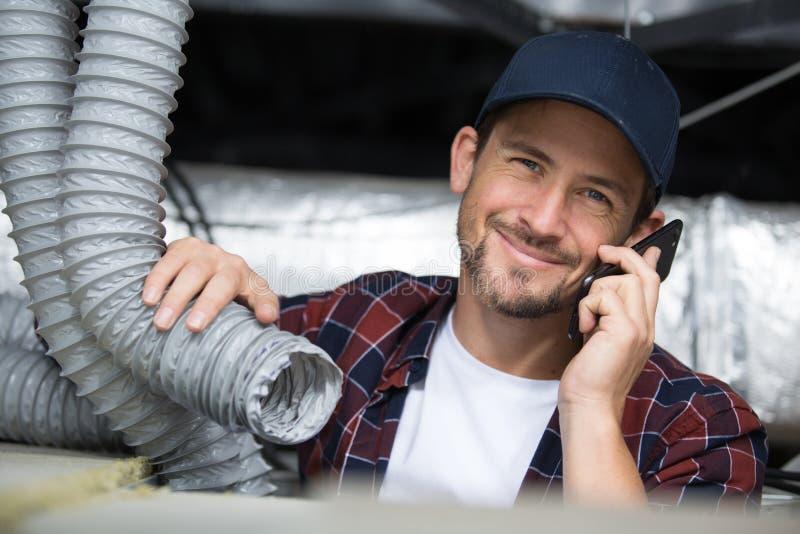Männliche Arbeitskraft, die Rohre bei der Anwendung des Telefons überprüft stockfoto