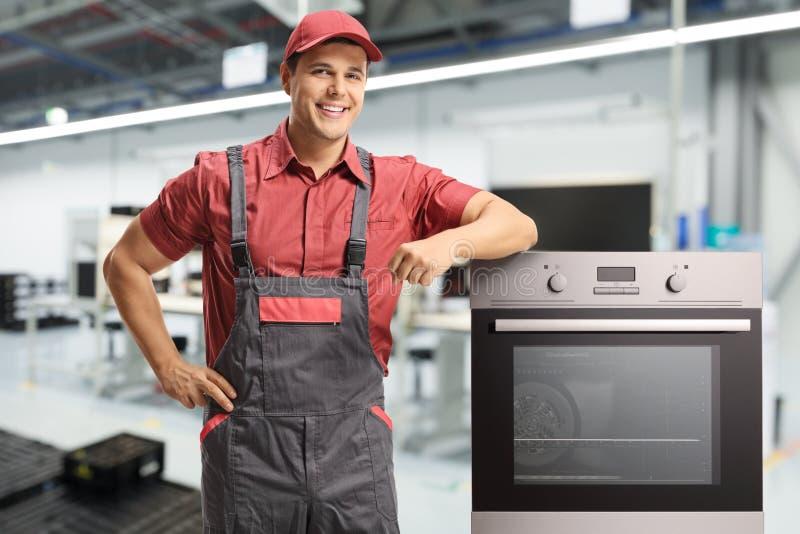 Männliche Arbeitskraft in einer einheitlichen Stellung nahe bei einem elektrischen Ofen stockbild