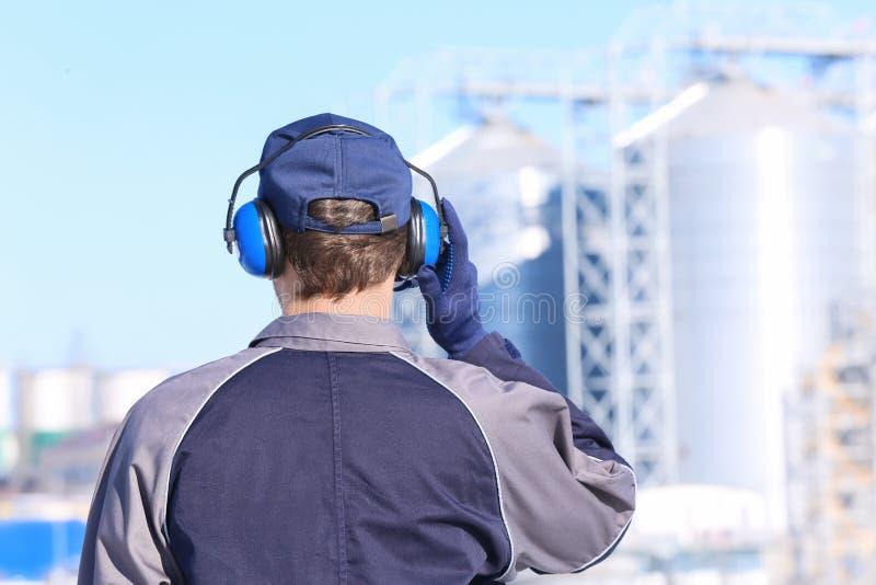 Männliche Arbeitskraft mit Kopfhörern draußen stockbild