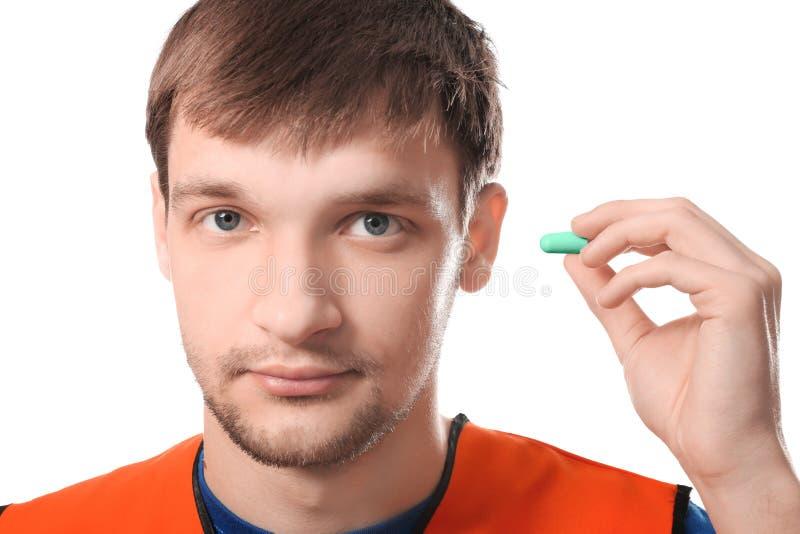 Männliche Arbeitskraft mit Ohrenpfropfen auf weißem Hintergrund stockfotos