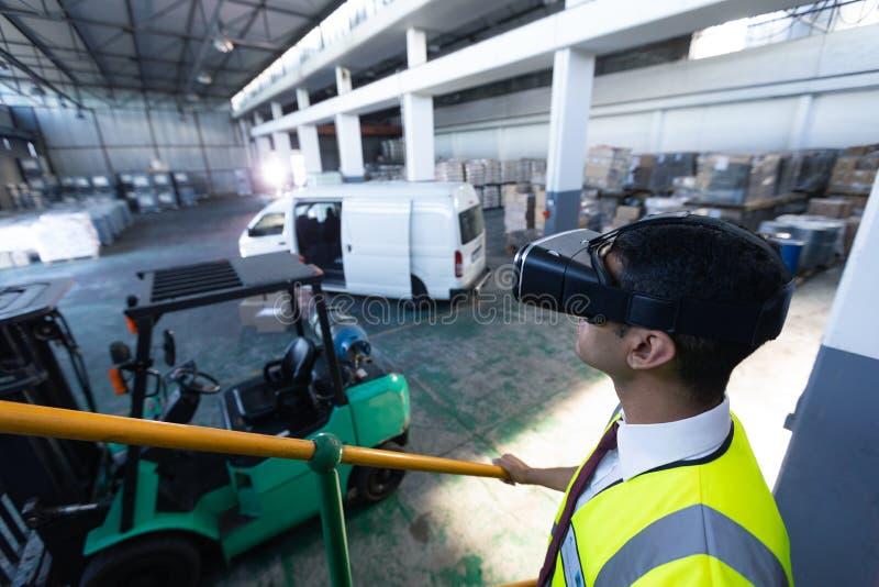 Männliche Aufsichtskraft, die Kopfhörer der virtuellen Realität im Lager verwendet lizenzfreies stockbild