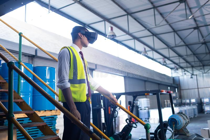 Männliche Aufsichtskraft, die Kopfhörer der virtuellen Realität im Lager verwendet stockfotos