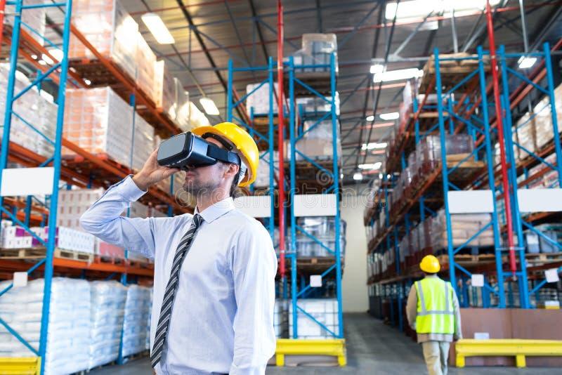 Männliche Aufsichtskraft, die Kopfhörer der virtuellen Realität im Lager verwendet lizenzfreie stockfotos