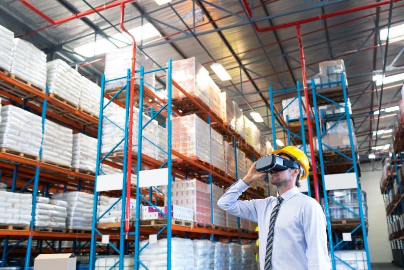 Männliche Aufsichtskraft, die Kopfhörer der virtuellen Realität im Lager verwendet lizenzfreie stockbilder
