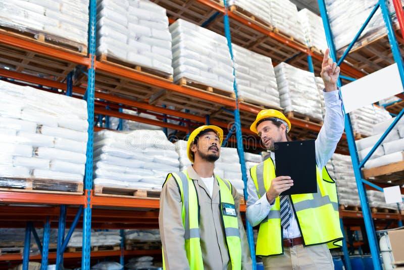 Männliche Aufsichtskraftstellung mit Arbeitskraft und Zeigen in Abstand im Lager lizenzfreies stockbild