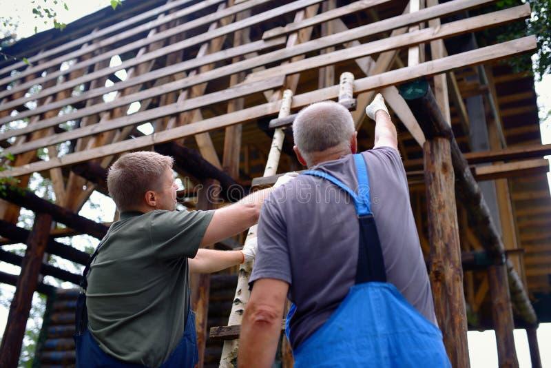 Männliche Bauarbeiter, die Baupläne über unfertigem Holzhaus besprechen stockfotografie