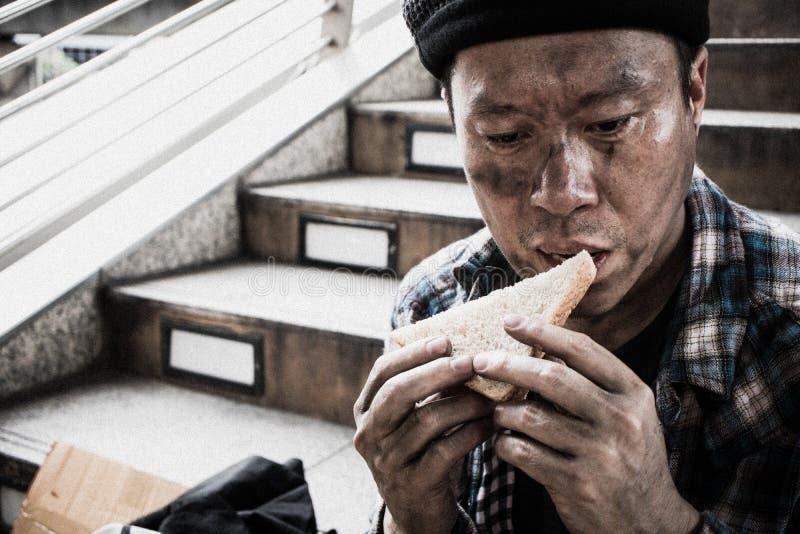 Männliche Bettlerhände, die Nahrungsmittel von der Menschenliebe essen stockfotos
