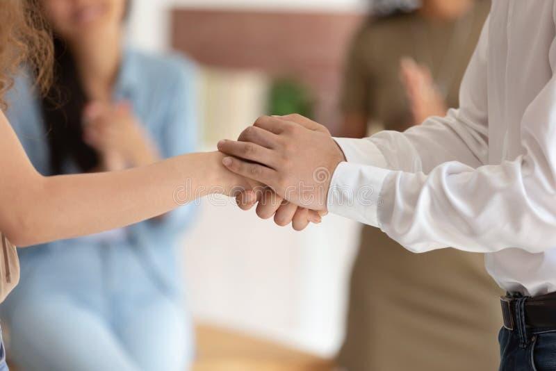 Männliche Chefholdinghand, die erfolgreiche Arbeitnehmerin, Vertrauenskonzept fördert lizenzfreie stockbilder